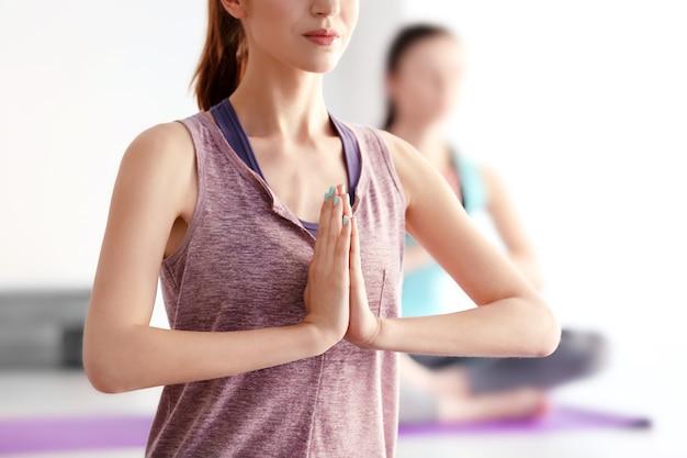 Giovani donne che fanno yoga in palestra