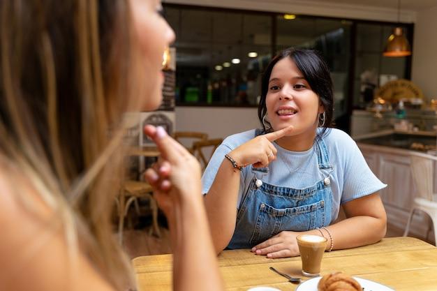 Giovani donne che bevono caffè e parlano nella lingua dei segni