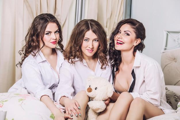 Amici di giovani donne in chat in camera da letto in camicie bianche