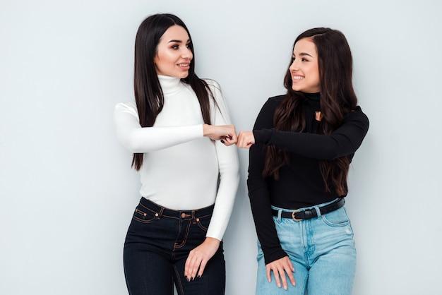 Le giovani donne si danno un pugno l'un l'altro