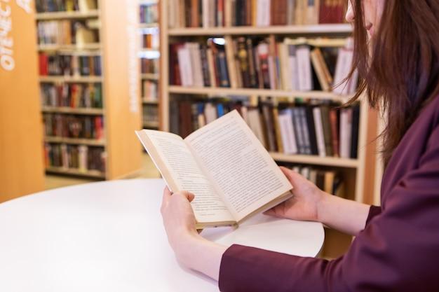 Mani delle giovani donne che tengono un libro. lettura in biblioteca, messa a fuoco selettiva, mani da vicino