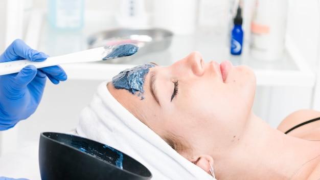 Le giovani donne che hanno una procedura di pulizia del viso nel salone di bellezza