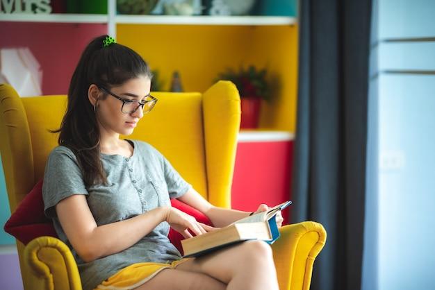 Le giovani donne stanno leggendo una letteratura di testo di un libro sul divano giallo nel soggiorno di casa, la giovane donna che indossa gli occhiali mentre legge il romanzo, il concetto di stile di vita, rilassarsi e divertirsi, isolare la casa