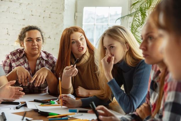 Giovani donne che preparano poster sui diritti e l'uguaglianza delle donne in ufficio. donne d'affari o impiegati caucasici si incontrano per problemi sul posto di lavoro, pressioni maschili e molestie.