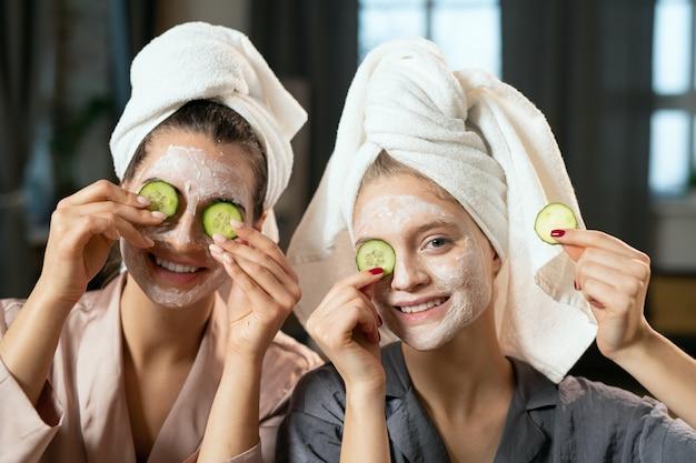 Giovani donne in pigiama di seta, asciugamani sulla testa, maschere di argilla sui volti e fette di cetriolo sugli occhi che si divertono e si godono la procedura di bellezza