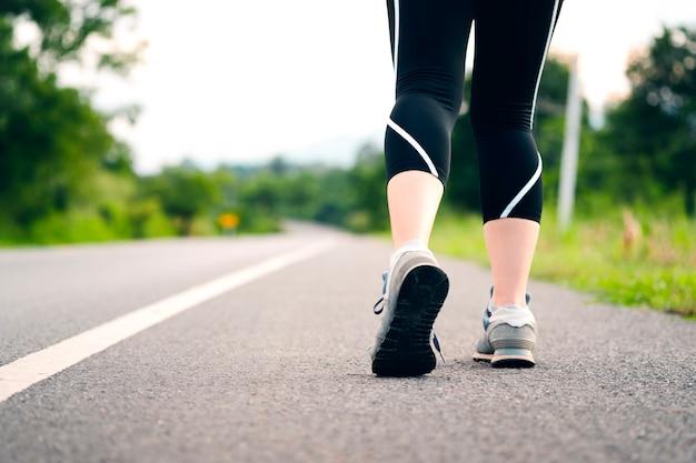 Le giovani donne stanno per prepararsi per camminare o fare jogging su una strada di campagna. vista posteriore delle gambe femminili. concetto di assistenza sanitaria con esercizio.
