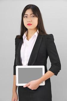 Giovani donne in piedi in tuta tenendo il suo computer tablet digitale