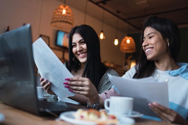 Giovani donne che studiano con i loro computer portatili in un bar.