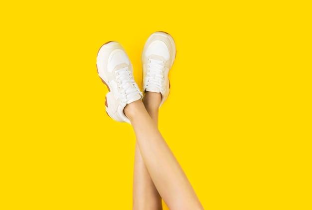 Giovani donne in eleganti scarpe da ginnastica su uno sfondo giallo.