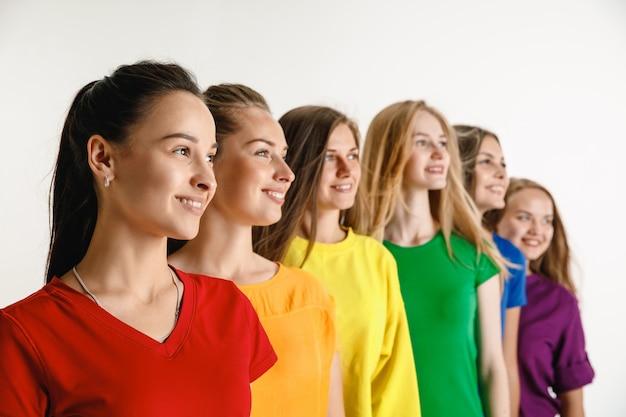 Le giovani donne hanno indossato nei colori della bandiera lgbt isolati sul concetto di orgoglio lgbt della parete bianca