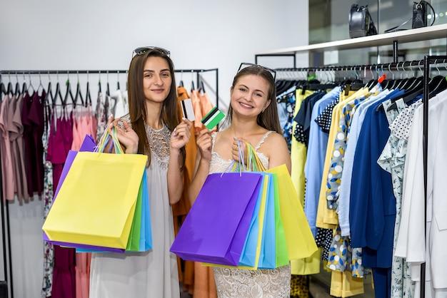 Giovani donne con carte di credito in posa nel reparto abbigliamento