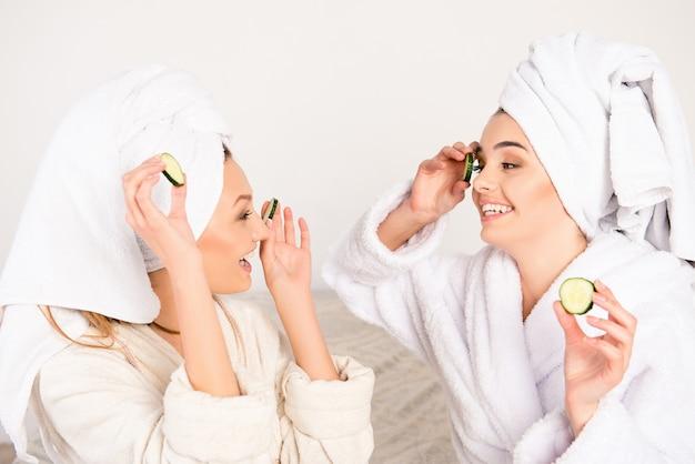 Giovani donne con cetrioli sugli occhi