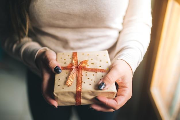 Giovani donne con unghie glitter che tengono la scatola del regalo di natale e la mostrano a porte chiuse. le mani tengono il contenitore di regalo del nuovo anno.