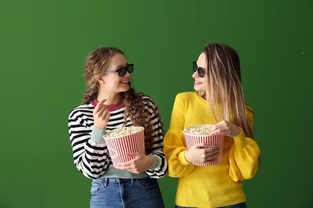 Giovani donne con popcorn che guardano film su sfondo colorato