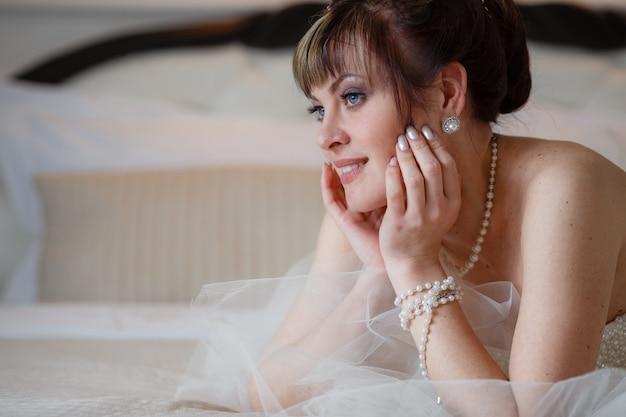 Giovani donne con abito da sposa nella stanza molto luminosa