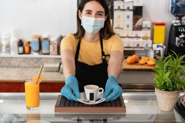 Giovane lavoratore che dà tazza di caffè all'interno del ristorante mentre indossa la maschera protettiva per il viso