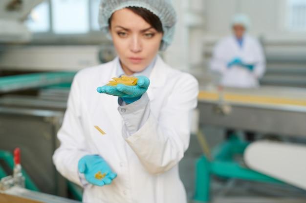Giovane operaio che controlla maccheroni