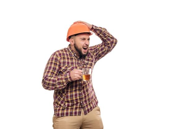 Il giovane operaio in un casco arancione tiene una tazza di tè, fondo bianco isolato