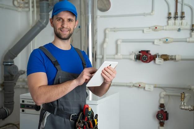 Il giovane operaio in una tuta protettiva utilizza un tablet mentre controlla l'attrezzatura della caldaia in casa
