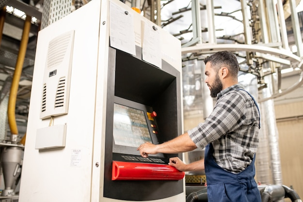 Giovane operaio in piedi dal pannello di controllo della linea di produzione e scegliendo le impostazioni di elaborazione in mostra