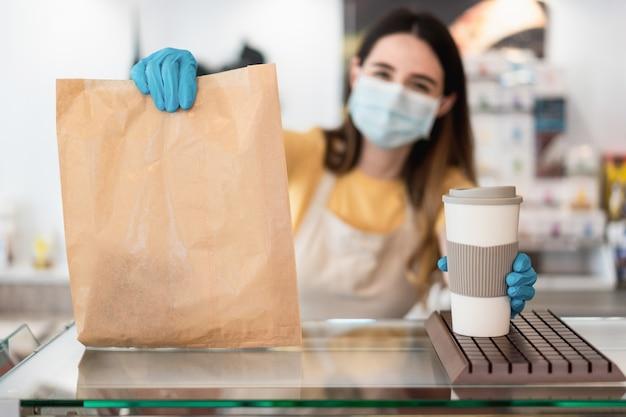 Donna giovane operaio offrendo cibo da asporto con maschera facciale