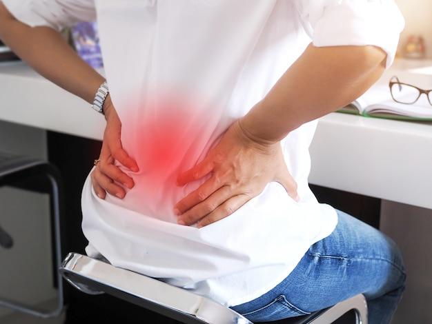 Giovane donna lavoratrice che si siede con il mal di schiena e la sofferenza del dolore alla vita. problemi di salute medica con dolori e mal di schiena concetto.