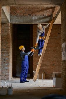 Giovane operaio in tuta blu e elmetto che dà la cassetta degli attrezzi al suo collega sulla scala
