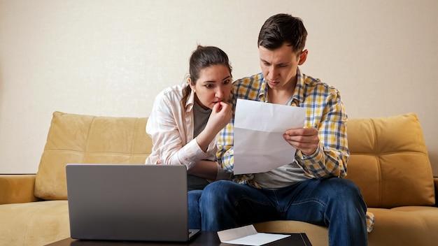 La giovane coppia di famiglia preoccupata apre la busta con una lettera di buone notizie dalla banca vicino al computer portatile seduto sul comodo divano beige nel soggiorno