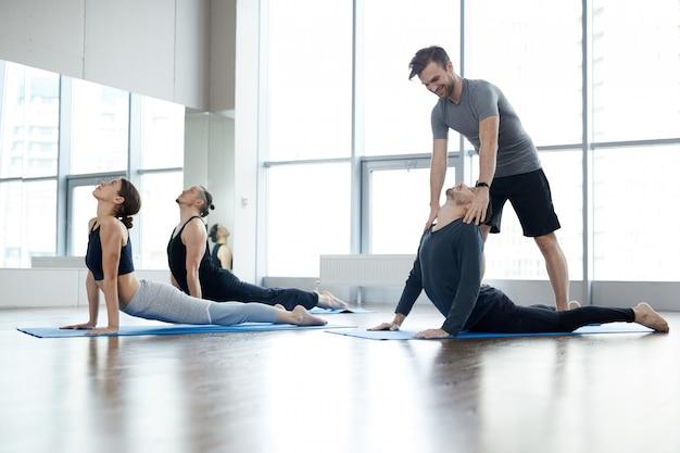 Giovane istruttore di yoga che corregge la posa della cobra degli studenti