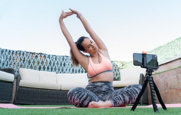Giovane insegnante di yoga che registra una lezione online con il suo telefono cellulare nel giardino di casa sua