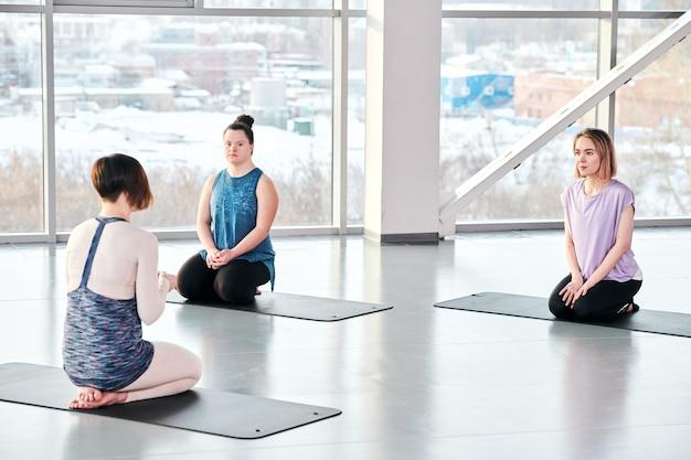 Giovane istruttore di yoga che dà consigli alle femmine attive sedute su stuoie davanti prima dell'inizio dell'allenamento fisico