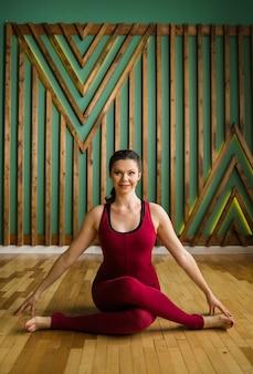 La giovane donna di yoga in abbigliamento sportivo marrone rossiccio si siede in un asana in una stanza