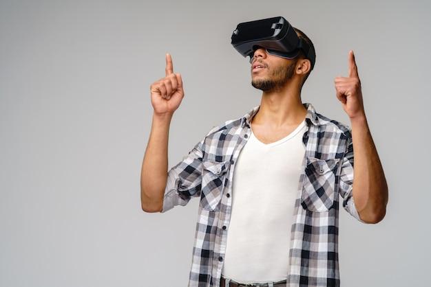 Giovane giovane che indossa le cuffie da realtà virtuale vr sul muro grigio chiaro