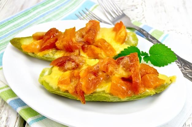 Giovani zucchine al forno in salsa aromatizzata con albicocca secca, panna e formaggio in un piatto bianco su un asciugamano sullo sfondo di tavole di legno chiaro
