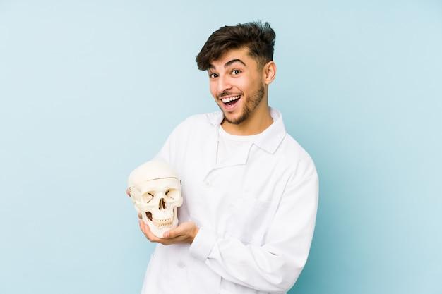 Uomo giovane medico che tiene un teschio ridendo e divertendosi