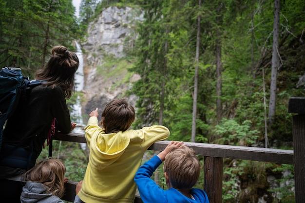 Giovane madre con tre bambini che guardano una bellissima cascata nel verde della natura estiva.