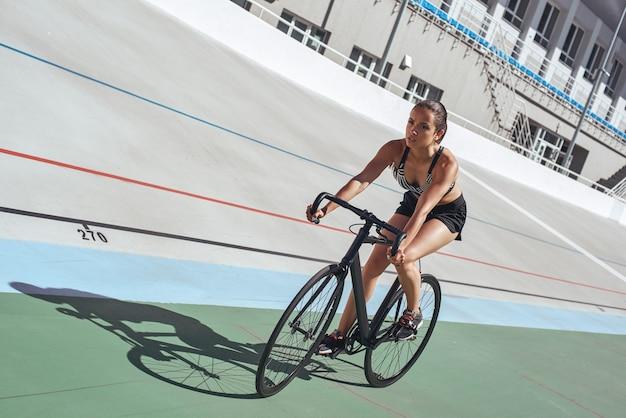Fai la tua migliore sportiva attraente in bicicletta in pista