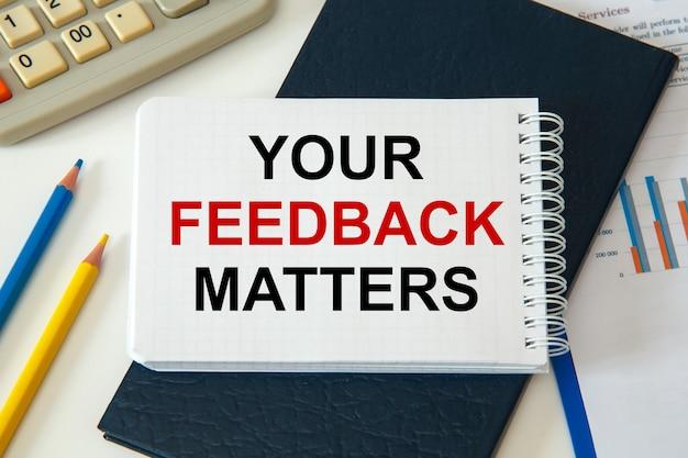 Il tuo feedback matters è scritto su un blocco note con accessori per ufficio.