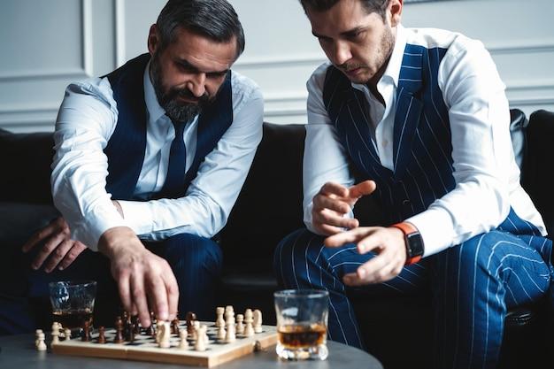 La tua mossa! due giovani uomini belli in giacca e cravatta che giocano a scacchi e sorridono seduti al chiuso.