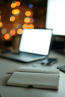 Per i tuoi appunti primo piano del notebook con la luce dello schermo del computer sullo sfondo su modern