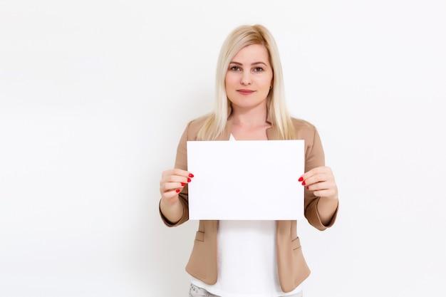 Il tuo testo qui. donna emozionante abbastanza giovane che tiene bordo in bianco vuoto. ritratto in studio su sfondo bianco. mock up per il design
