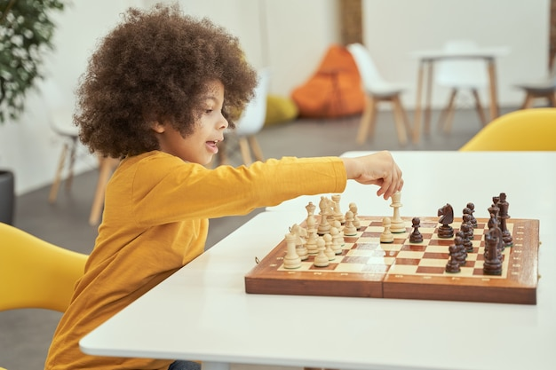 Il tuo turno ragazzino intelligente che sembra felice mentre gioca a scacchi seduto al tavolo in casa