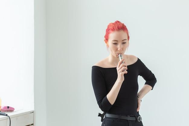 Concetto di gioventù e dipendenza - giovane donna dai capelli rossi che fuma vape vicino alla finestra.