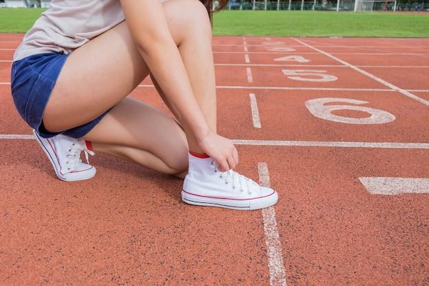 Giovanissimo corridore adolescente che lega i lacci delle scarpe a correre in pista