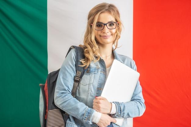 Studentessa giovanile con bandiera d'italia sullo sfondo.