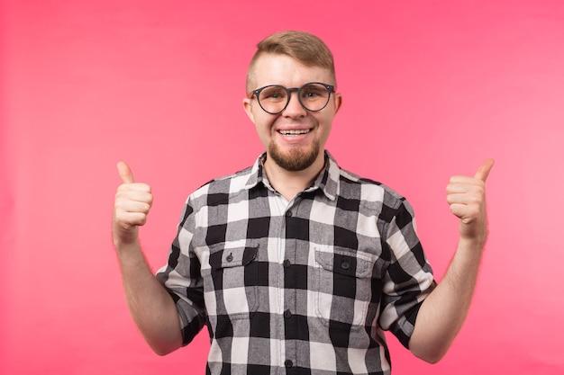 Gioventù, gesto e buon concetto: il giovane sembra un nerd mostraci il pollice in alto sulla superficie rosa.