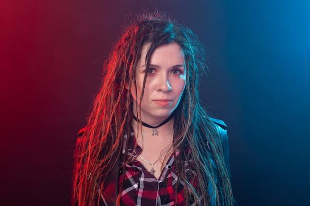 Gioventù, acconciatura e concetto moderno - giovane donna con i dreadlocks sopra la luce rossa e blu