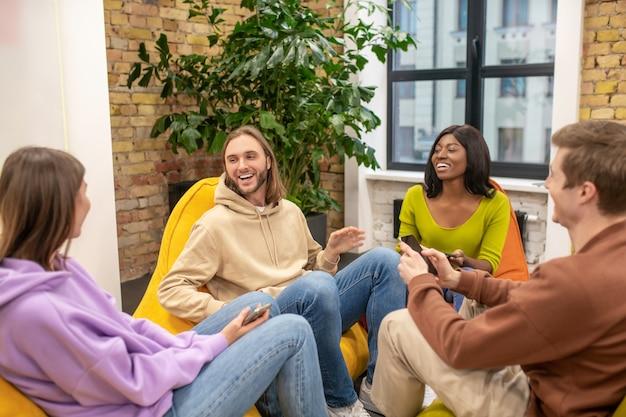 Gioventù, passatempo. gruppo di giovani leader in jeans e maglioni che comunicano divertendosi seduti sulle poltrone nell'area ricreativa dell'ufficio