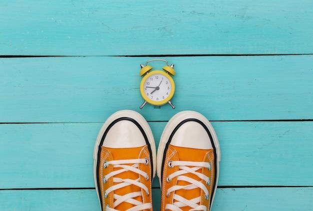 Sneakers retrò giovanile e mini sveglia su uno sfondo di legno blu. Foto Premium
