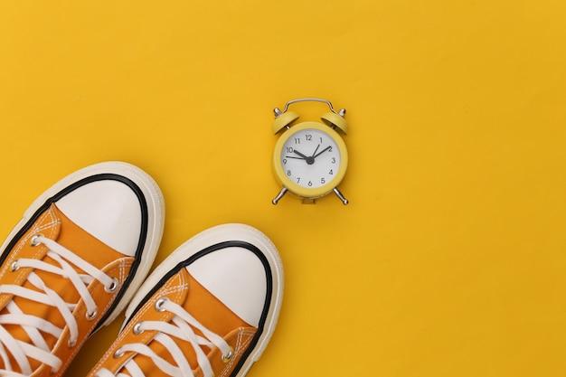 Sneakers retrò giovanile e mini sveglia su sfondo giallo. Foto Premium